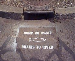 A storm drain stencil that reads, &#34Dump no waste, drains to river.&#34