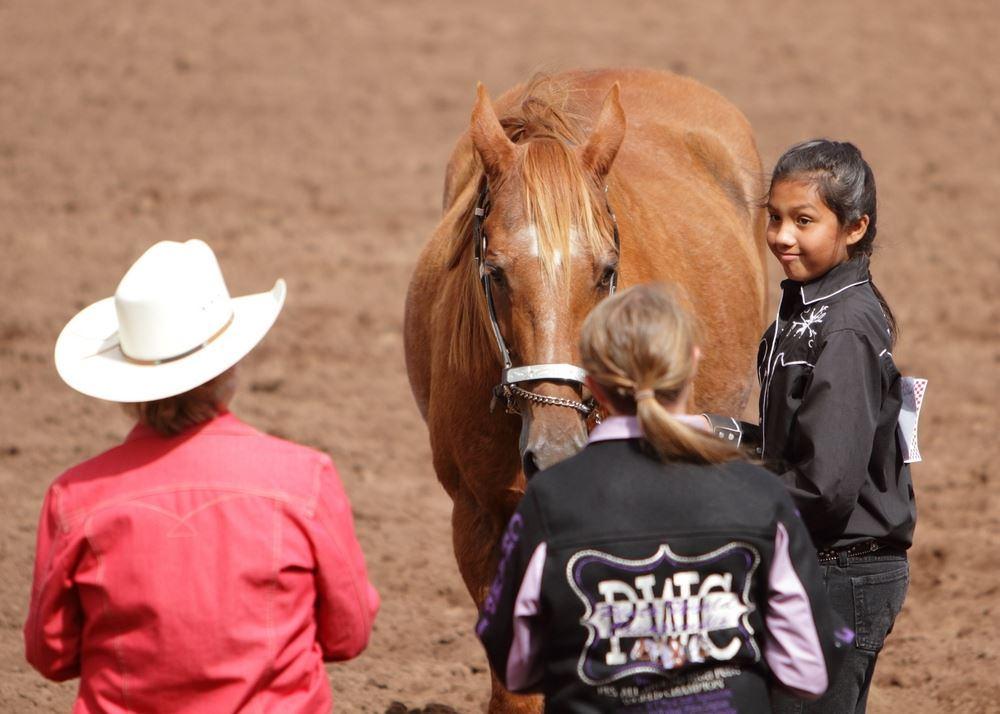 A girl stand next to her horse in the arena at the 2014 Klickitat County Fair.