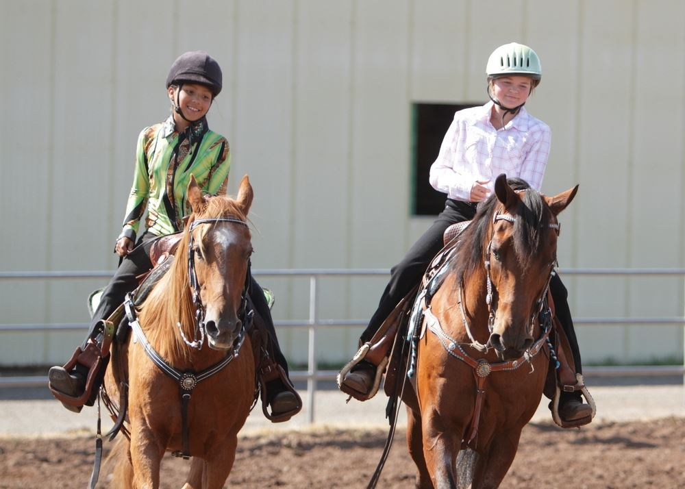 Two girls ride their horses in the arena at the 2014 Klickitat County Fair.