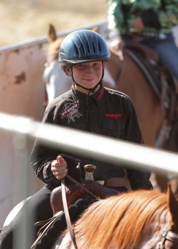 A  young man smiles as he rides his horse in the arena at the 2014 Klickitat County Fair.