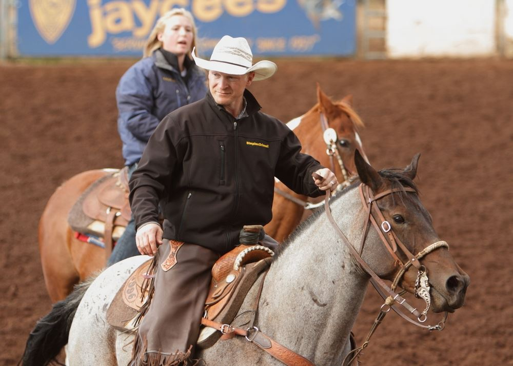 A man and woman sit on their horses in the arena at the 2014 Klickitat County Fair.