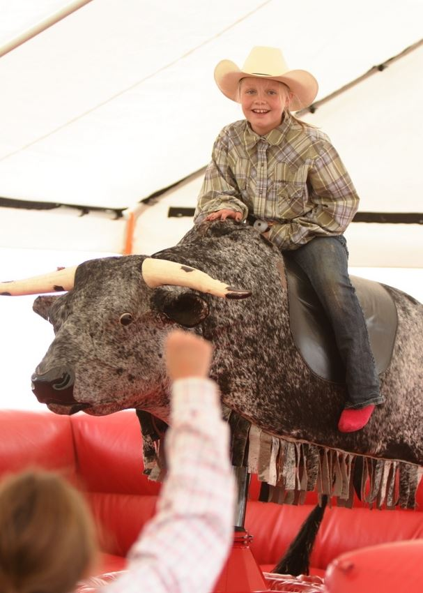A little girl gets ready to attempt a ride on the mechanical bull at the 2014 Klickitat County Fair.