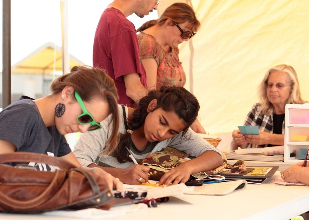 Girls write on paper at an exhibit for the 2014 Klickitat County Fair.