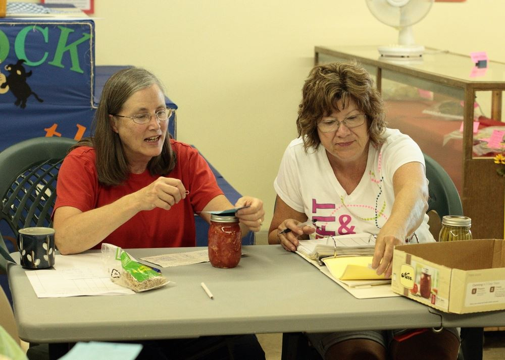 Two women sit at an exhibit for the 2014 Klickitat County Fair.
