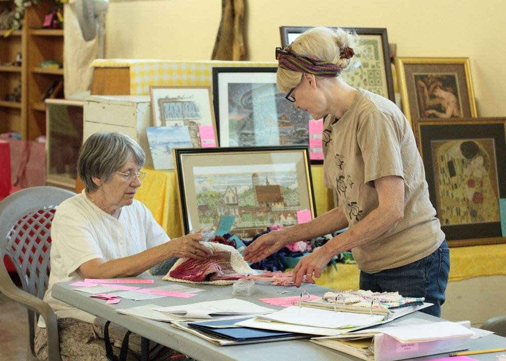 Two women discuss knitted items at the 2014 Klickitat County Fair.