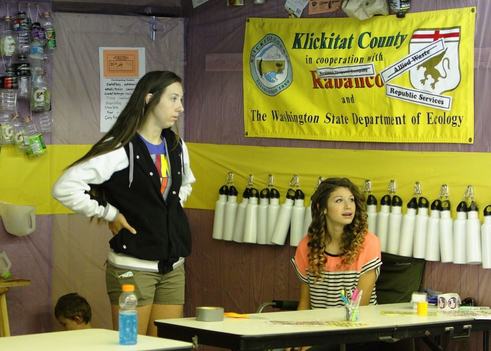 Two girls sit at the Waste Reduction exhibit at the 2014 Klickitat County Fair.