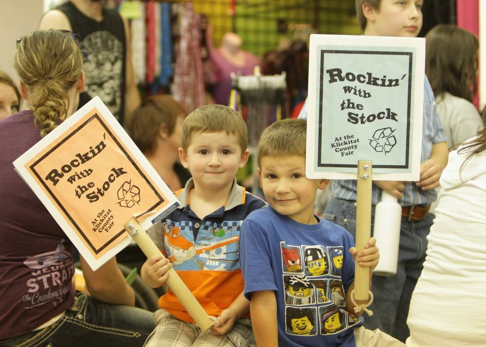 Two little boys hold Rockin' with the Stock signs.