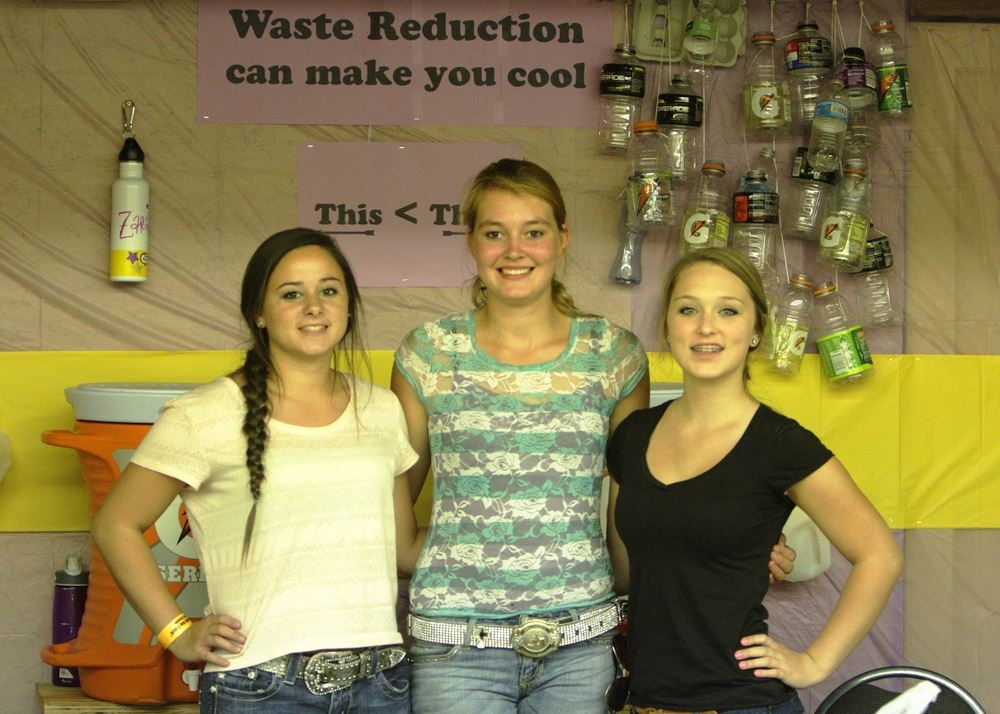 Three girls pose at the Waste Reduction exhibit.
