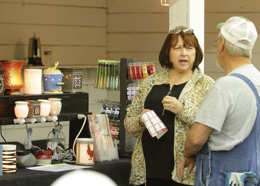 A woman talks to a man at the Scentsy exhibit at the 2014 Klickitat County Fair.