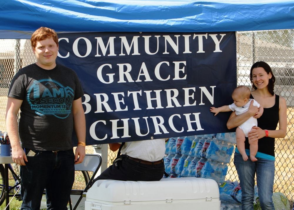 A man and a woman holding a baby stand at the Community Grace Brethren Church exhibit.