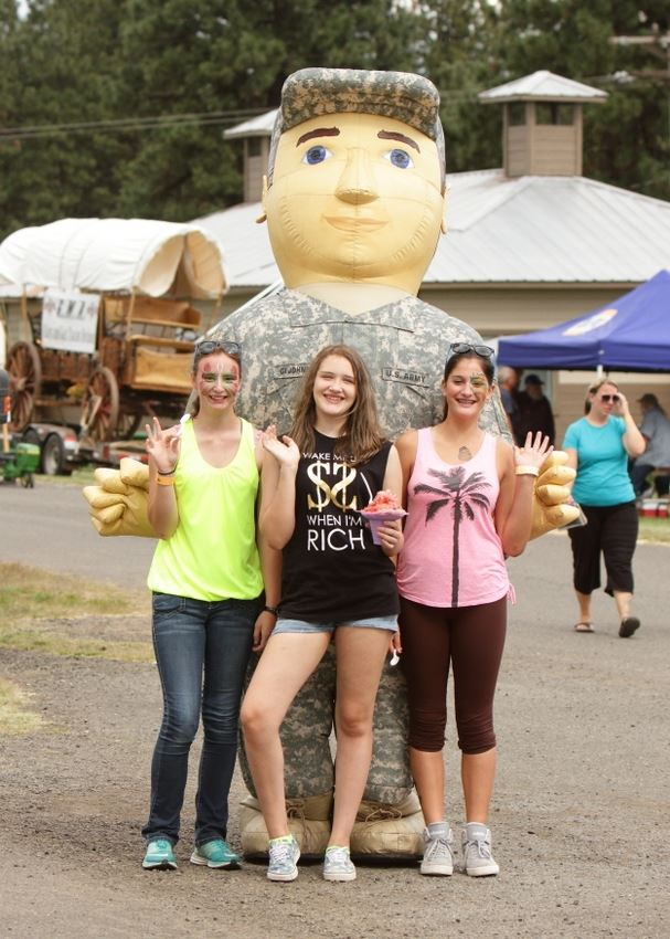 Three girls pose with the blow up Army man.