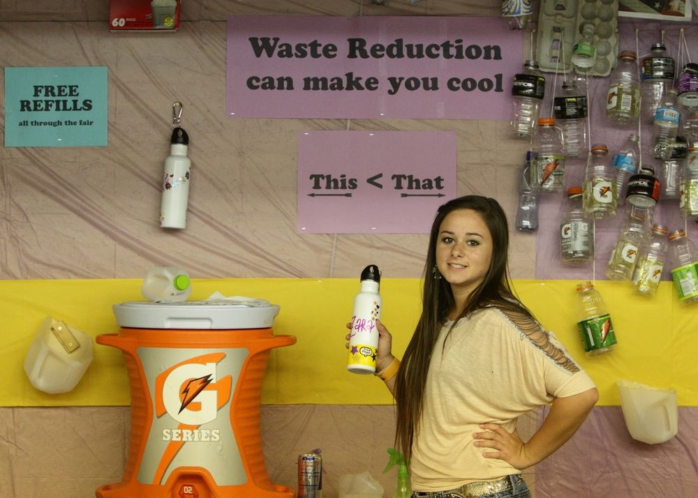 A girl holds her reusable water bottle at the Waste Reduction exhibit.