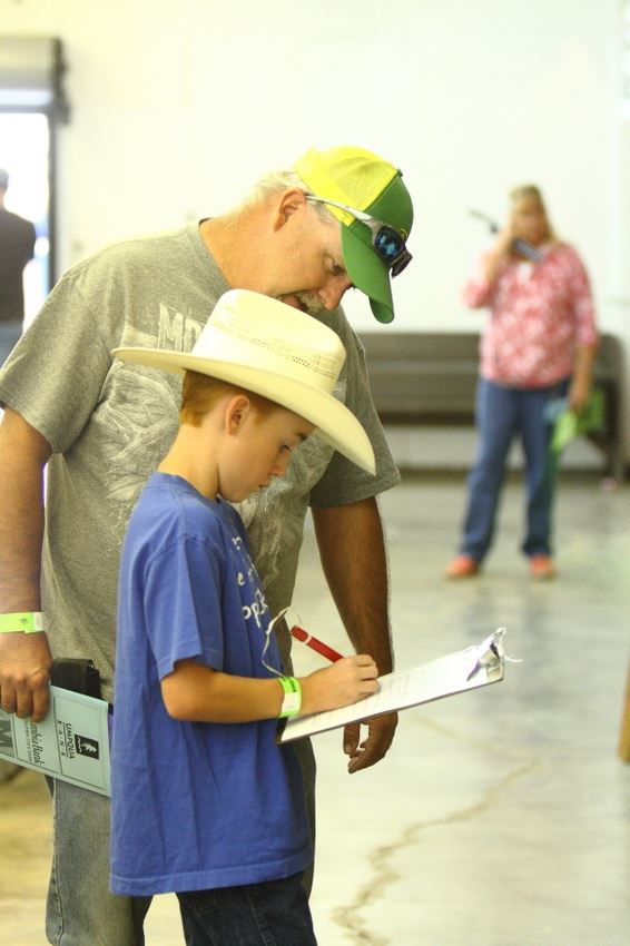 A little boy signs a piece of paper at the 2014 Klickitat County Fair.