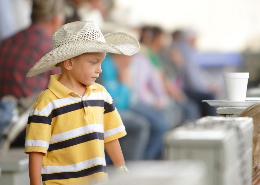 A little boy in a cowboy hat stands in front of the crowd at the 2014 Klickitat County Fair.