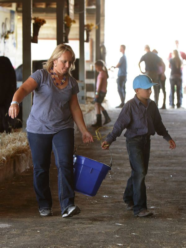 Woman and little boy carry a blue bucket together.