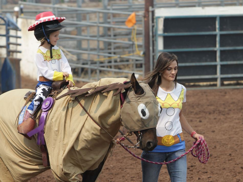 Woman walks a horse dressed as Bullseye, carrying a little girl dressed as Jessie from Toy Story 2.