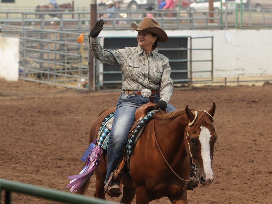 Woman waves to a crowd atop her horse.