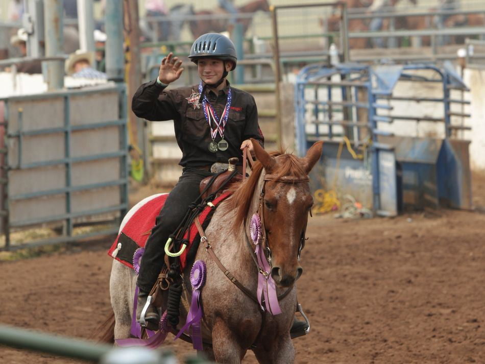 Young man rides his horse and waves to the crowd of the Klickitat County Fair.