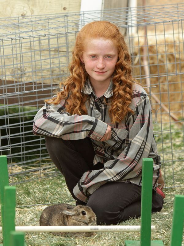A girl kneels down next to her rabbit at the 2015 Klickitat County Fair.