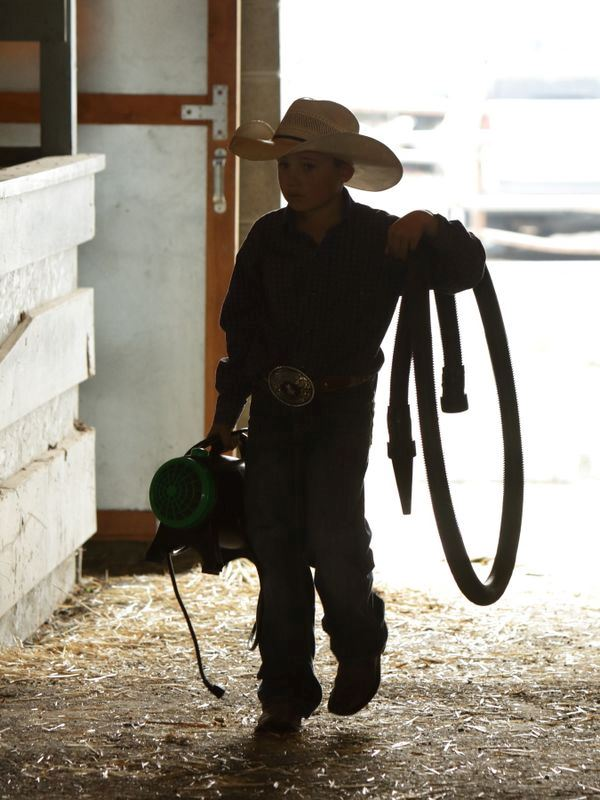 A boy carries some equipment in the animal barn at the Klickitat County Fair.