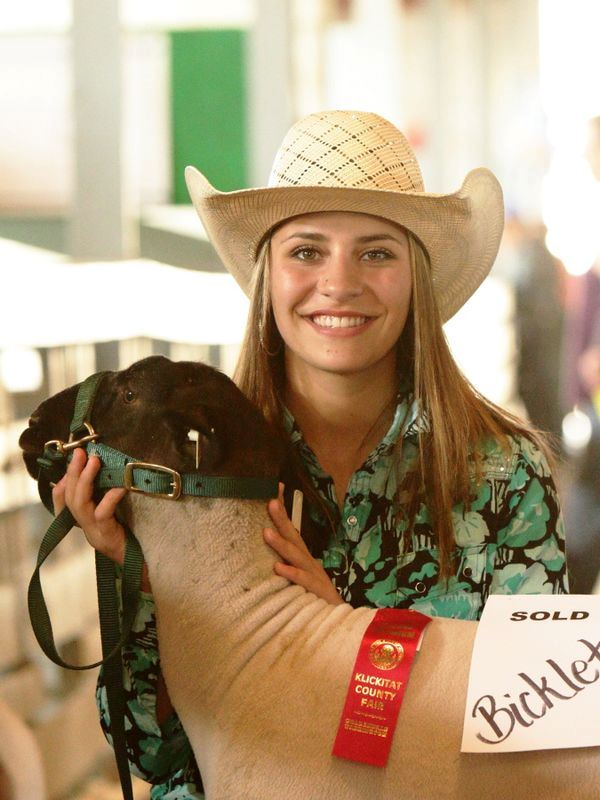A girl smiles holding the head of her show sheep.