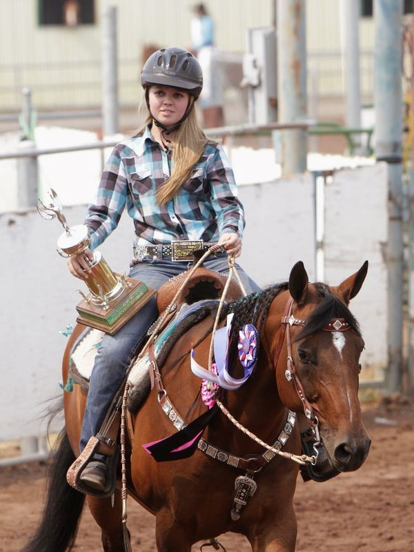 A girl rides her horse holding a trophy.