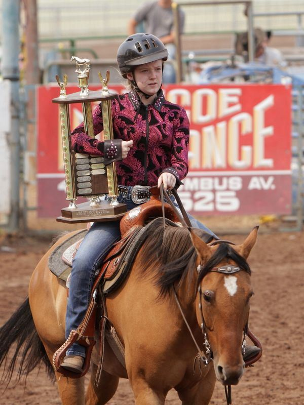 A girl rides her horse holding a large trophy.