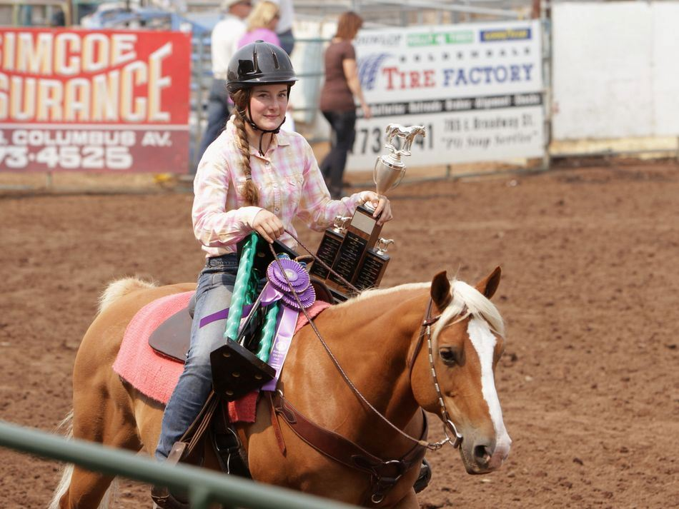 A girl riding her horse carries two trophies.