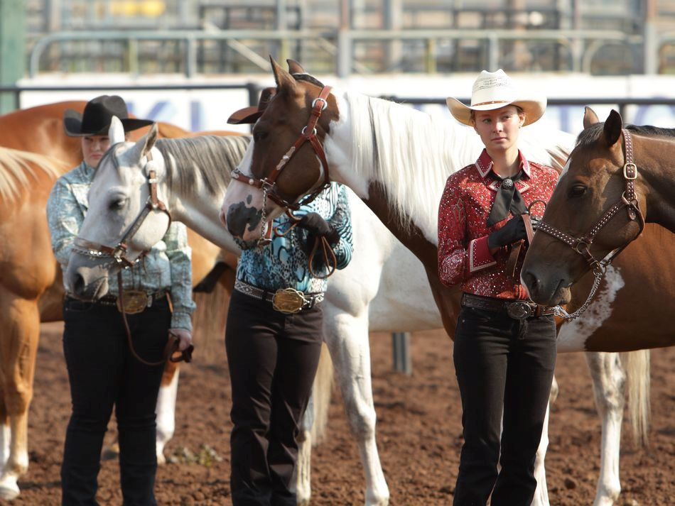 Young women stand next to their horses at the 2015 Klickitat County Fair.