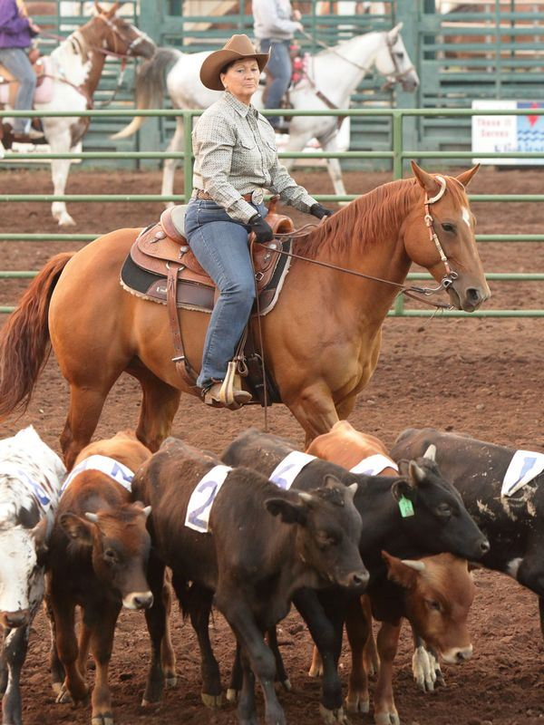 A woman herds calves on her horse at the 2015 Klickitat County Fair.