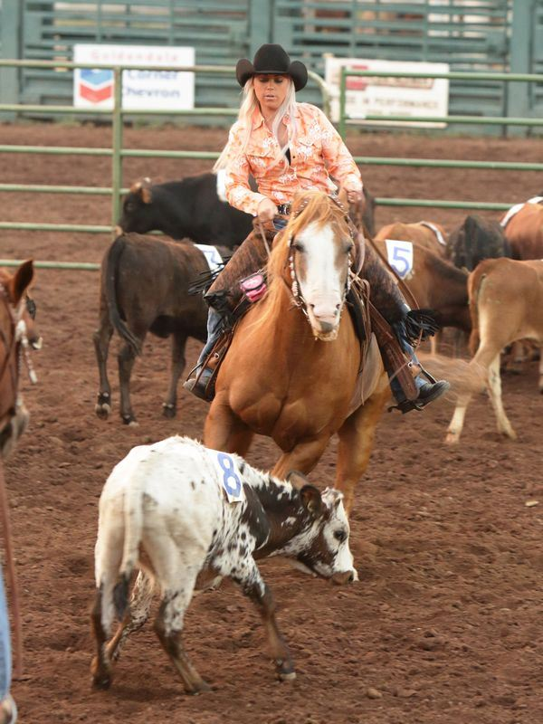 A young woman herds calves on her horse at the 2015 Klickitat County Fair.
