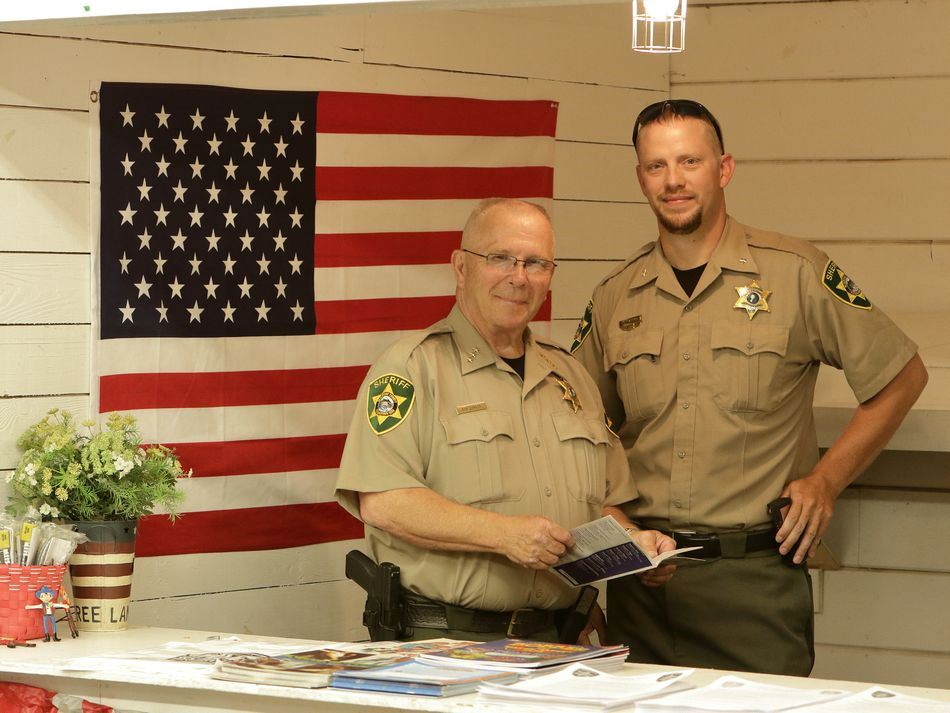 Members of the Klickitat County Sheriff's Department stand at an exhibit.