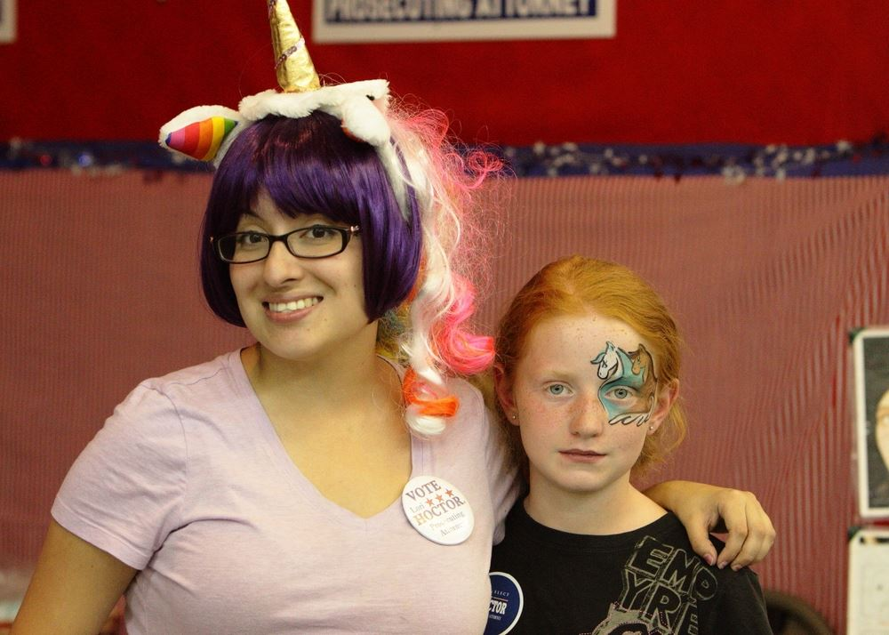 A woman with a unicorn wig and a little gir with face paint smile at the 2014 Klickitat County Fair.