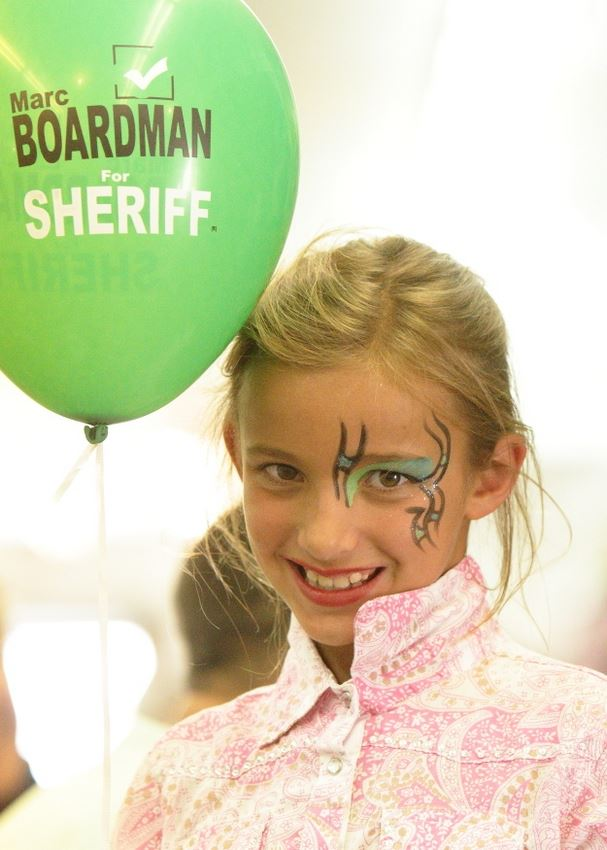 A little girl with her face painted holds a green balloon.