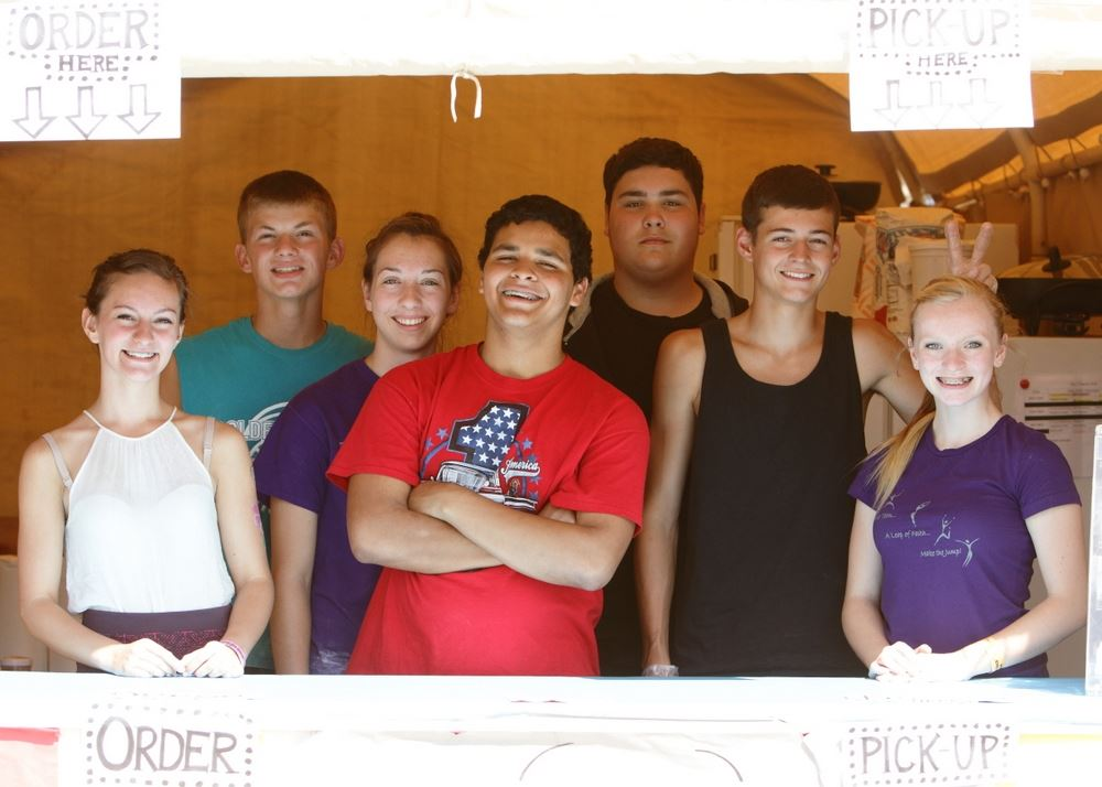 A group of teens stand together at a booth at the 2014 Klickitat County Fair.