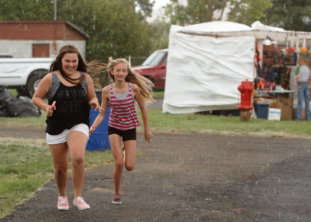 Two girls run through the rain together at the 2014 Klickitat County Fair.