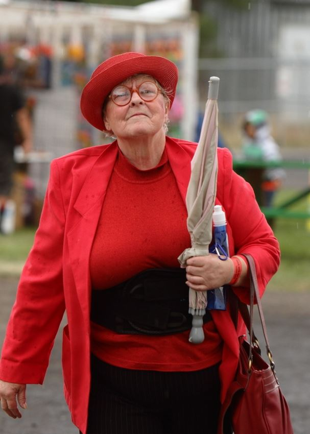 A woman clad in all red holds her umbrella in front of her intently.