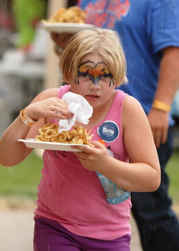 A little girl eats some curly fries at the 2014 Klickitat County Fair.