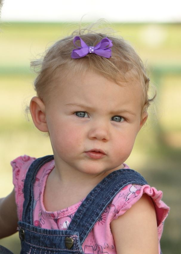 A baby girl with a purple bow in her hair attends the 2014 Klickitat County Fair.