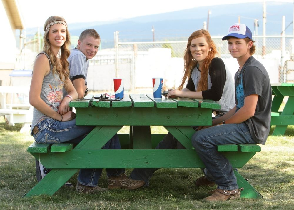 A group of teens sit together at a green picnic table.