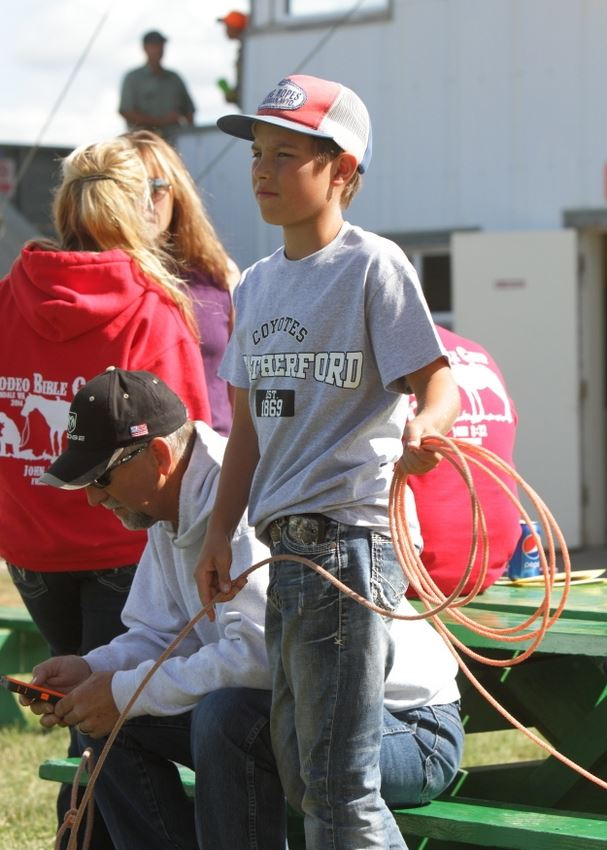 A boy wearing a King Ropes hat works on his lasso.