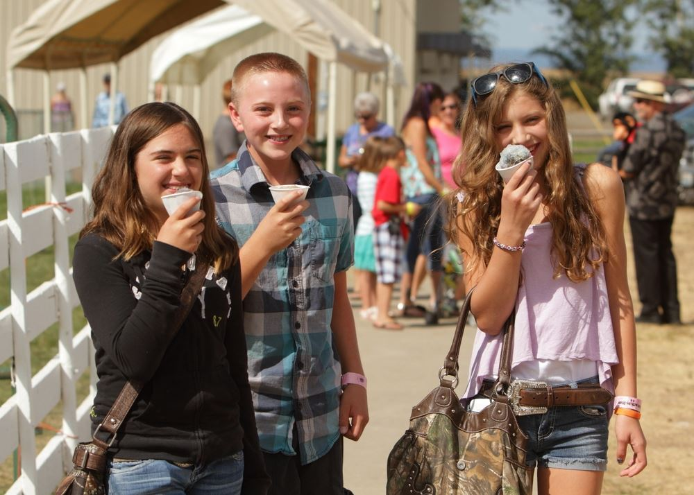 A group of kids eat snow cones together at the 2014 Klickitat County Fair.