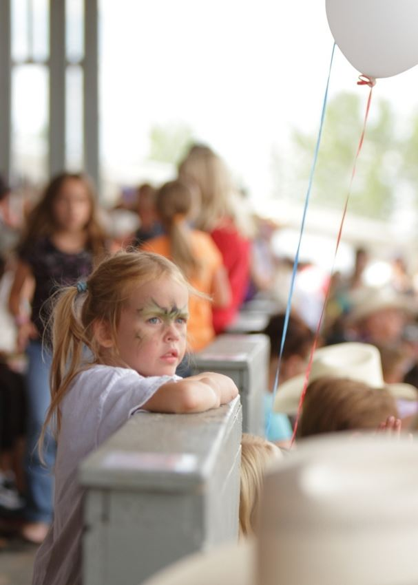 A little girl leans on a fence at the 2014 Klickitat County Fair.