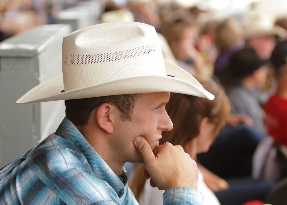 A man in a cowboy hat sits among the 2014 Klickitat County Fair.