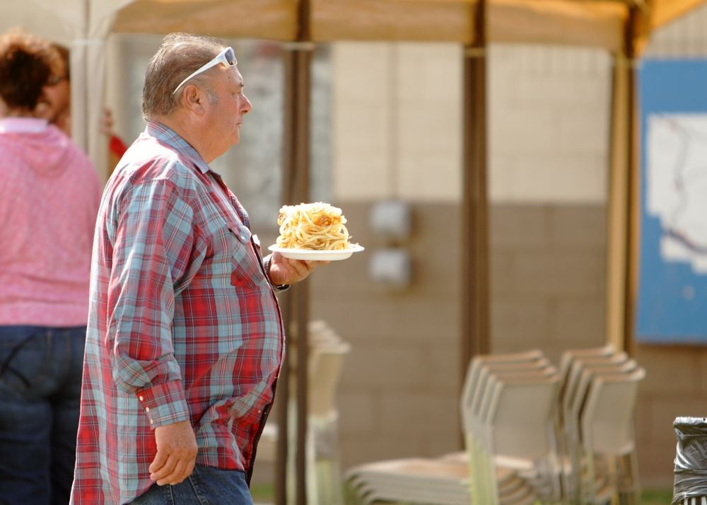 A man holds a plate of curly fries at the 2014 Klickitat County Fair.