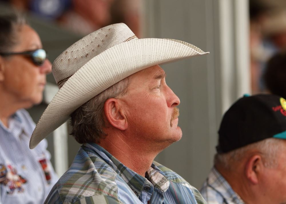 A man in a cowboy hat sits among the crowd at the 2014 Klickitat County Fair.