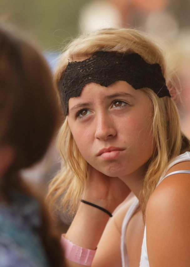 A girl with a black head band on sits among the crowd at the 2014 Klickitat County Fair.