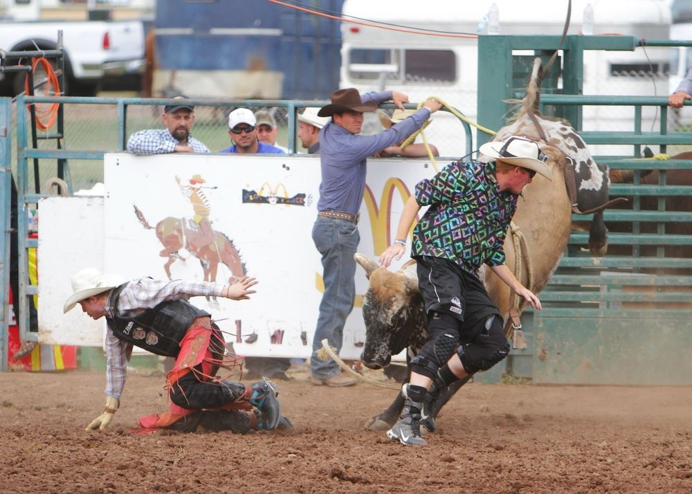 A man runs to safety from as a bucking bull is distracted at the 2014 Klickitat County Fair Rodeo.