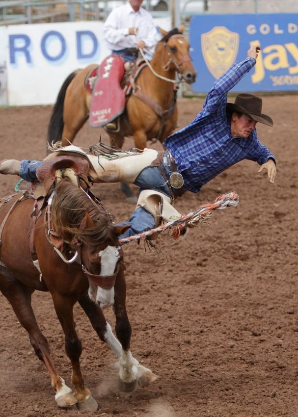 A man leaps from a bucking horse at the 2014 Klickitat County Fair Rodeo.