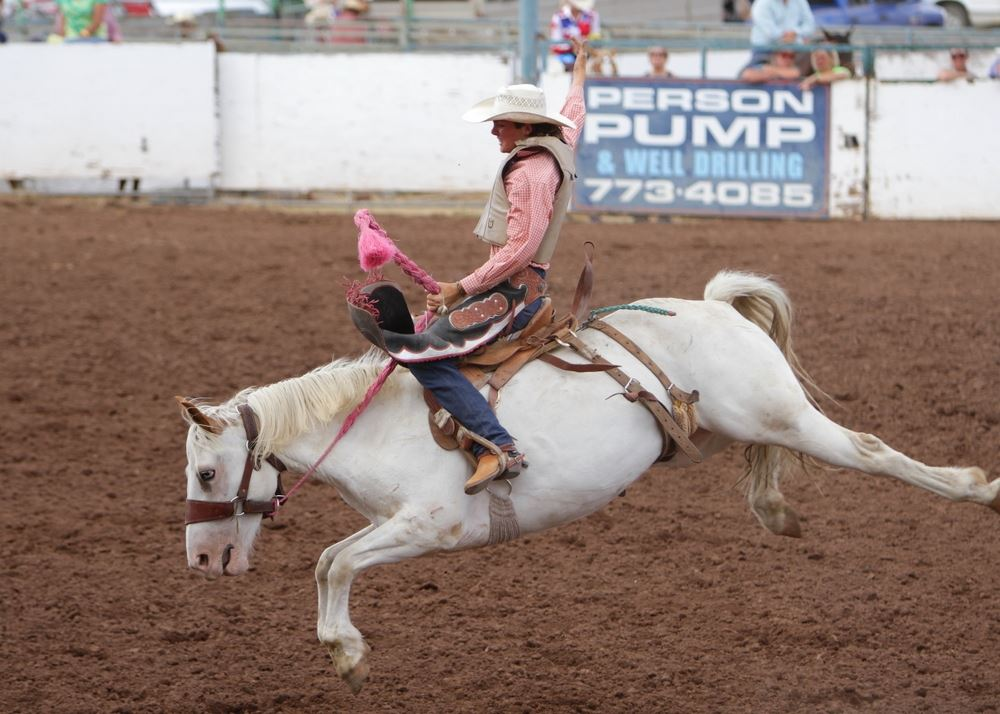 A woman holds tight as he horse bucks at the 2014 Klickitat County Fair Rodeo.